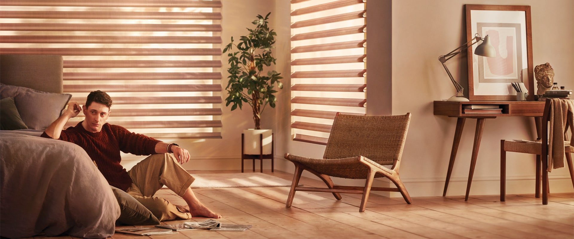 Man sitting on bedroom floor next to Pirouette Window Shadings