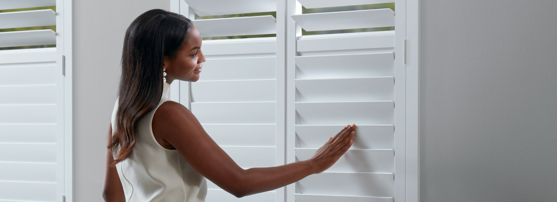 Woman closing NewStyle Shutters with SoftClose Louvers
