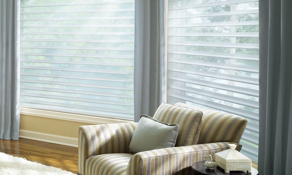 Silhouette window shadings with drapes in a sitting room