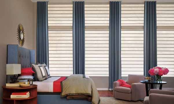 Vignette roman shades with drapes in a bedroom
