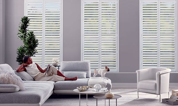 Woman lounging on couch in front of NewStyle Shutters