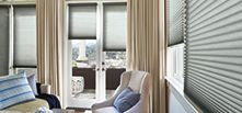 Alustra Duette honeycomb shades with drapes in living room