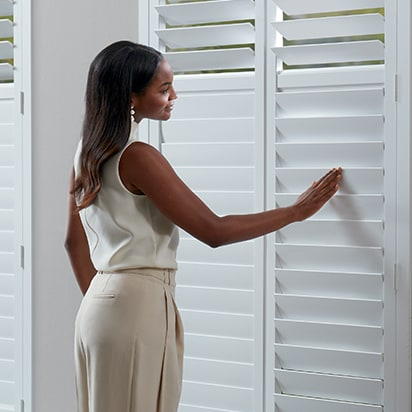 Woman closing NewStyle Shutters with SoftClose Louvers.